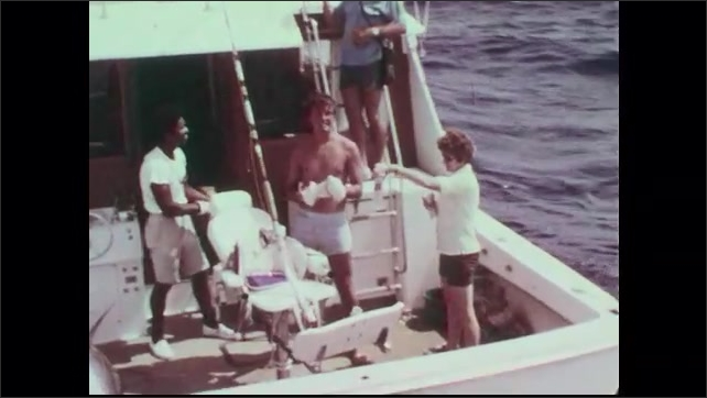 1960s: Men lift tuna onto fish hook on back of boat. Woman hands drinks to men. Captain hangs fish flag on boat.