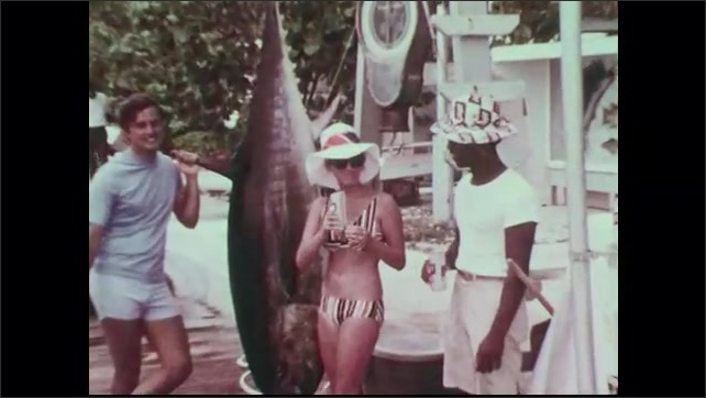 1960s: Men stand around weigh station next to tuna. Men shake hands. Woman stands next to strung up tuna, drinks. Kids look at tuna. Boats anchored at dock. Dogs walk on dock.