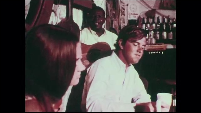 1960s: Men walk down dock, past tuna on display, carry cooler. Fishing boats at dock. Man sits at a table with two women, drinks. Man plays guitar in background.
