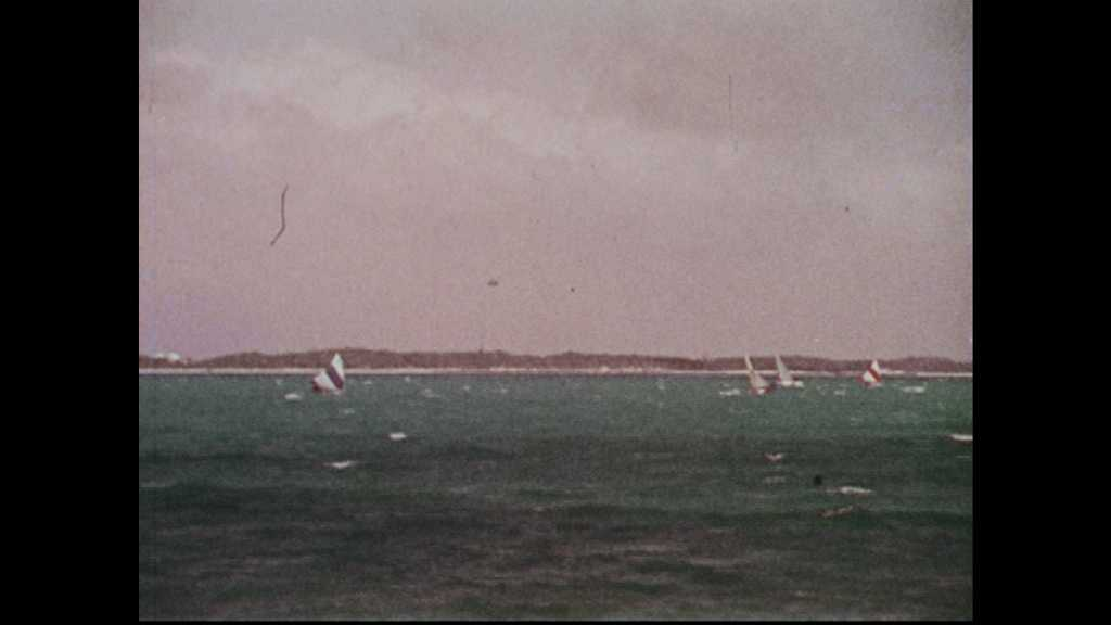 1960s: Sailboats on the ocean horizon. Boats tied up on water. Woman in bikini walks on sand beach.