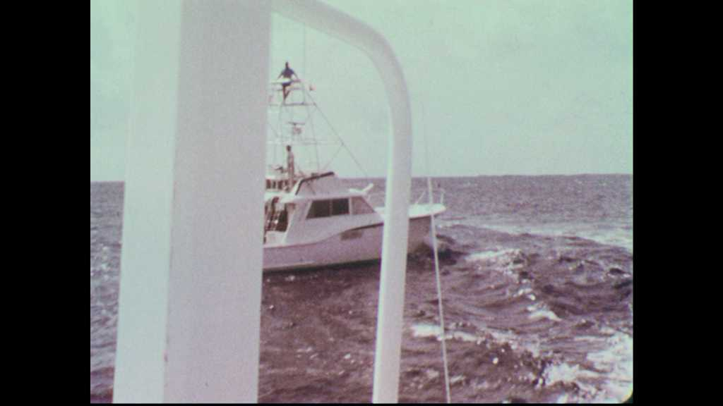 1960s: Deep-sea fishing boat with tuna tower on ocean. Fisherman cleans fish on shore.