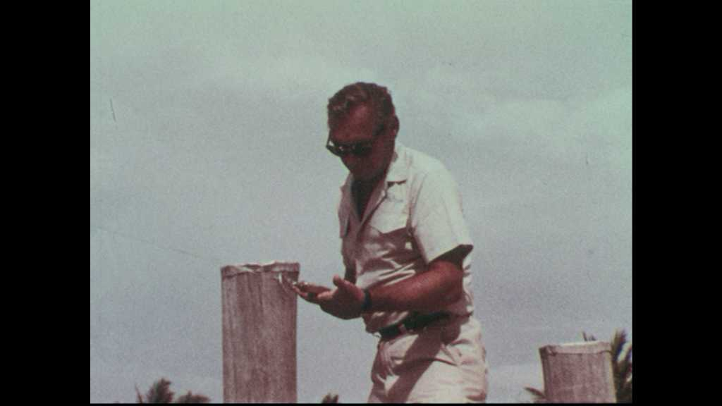 1960's: Man tests high test fishing line and hook from deck.  Sonar on boat. Man steers wheel on boat. Boat depart wharf. Wake behind boat. Deckhand adjusts safety lines on boat.
