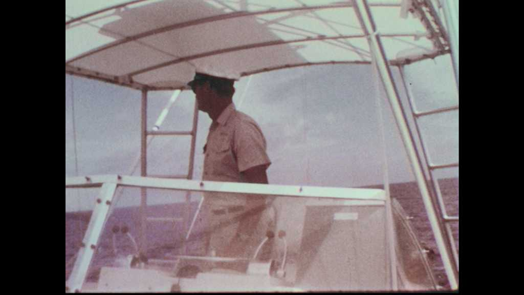 1960s: Captain on fishing boat. Fisherman waits strapped into a fighting chair on boat deck. Pennant flag waves in wind. Deckhand in Schlitz hat looks overboard.