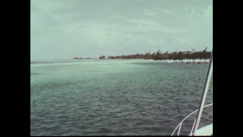 1960s: Fishing boat approaches Bimini Island shore. Dinghy brings supply of Schlitz beer to boat, loaded by deckhand wearing Schlitz hat.