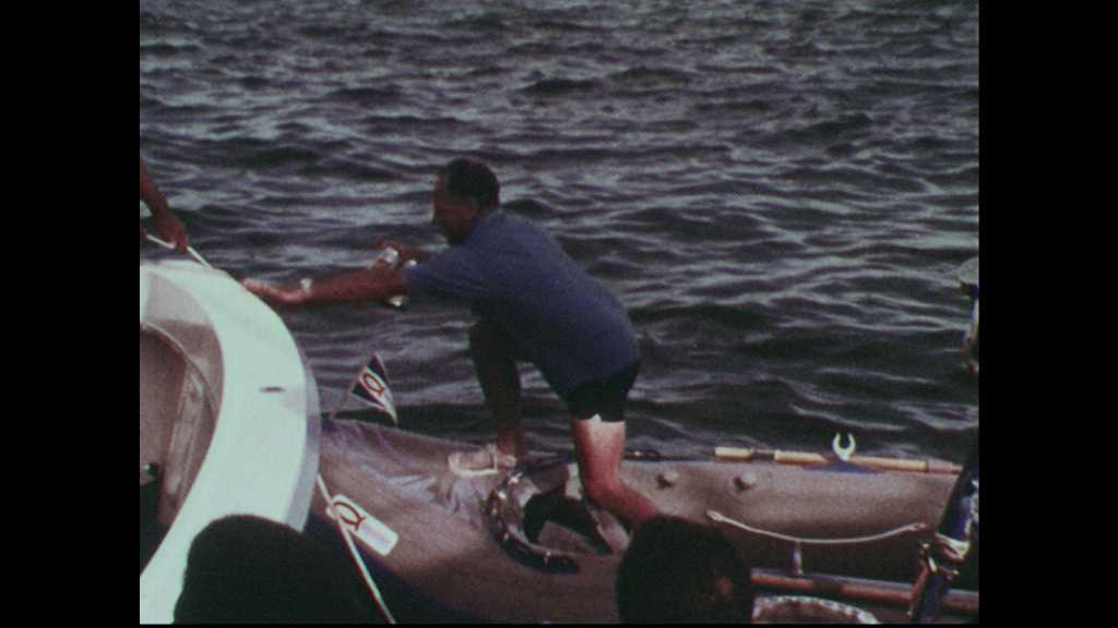 1960s: Dinghy captain hands six-pack of Schlitz to deckhand and falls overboard into the water. He surfaces holding Schlitz and hands it to the deckhand from the water. Scuba gear on the deck.