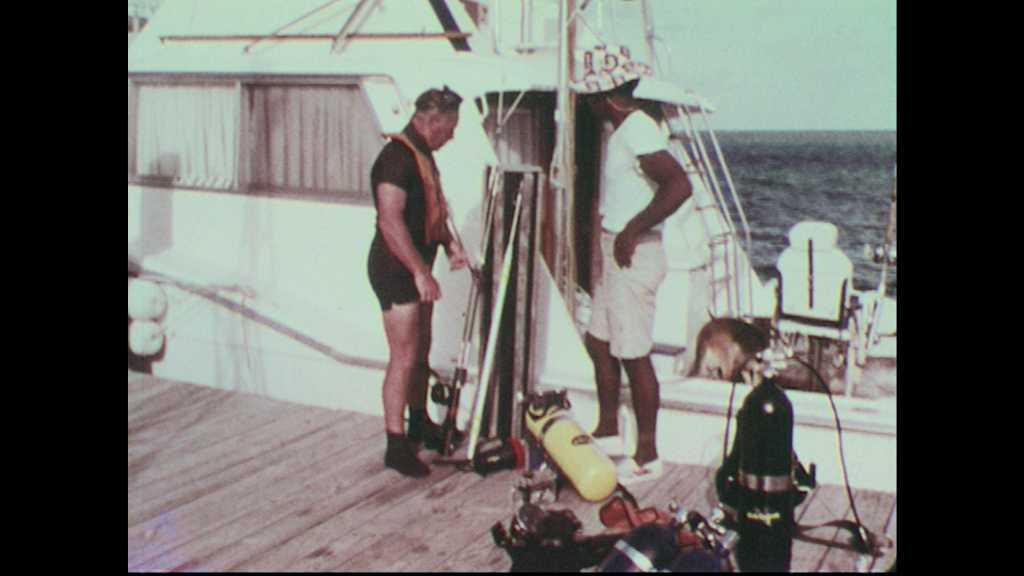 1960s: Scuba diver demonstrates pole spear for use on sharks to deckhand. Scuba diver points to M16 bullet at top of spear.