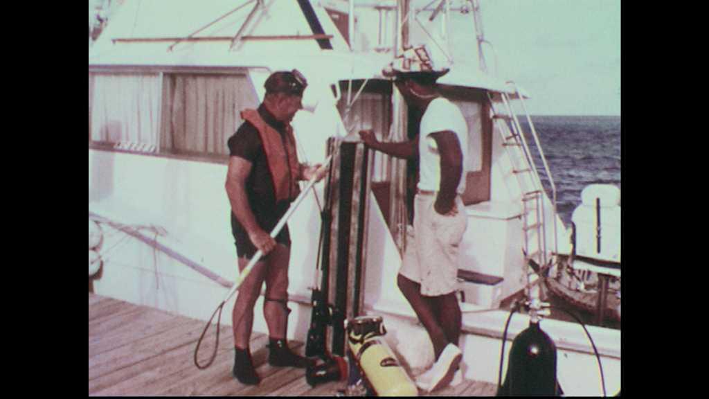 1960s: Scuba diver demonstrates double-barreled underwater spear gun.