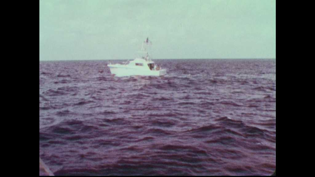 1960s: Deep-sea fishing boat on waves. Sonar machine on deck. Fishermen troll from back of quickly moving boat.