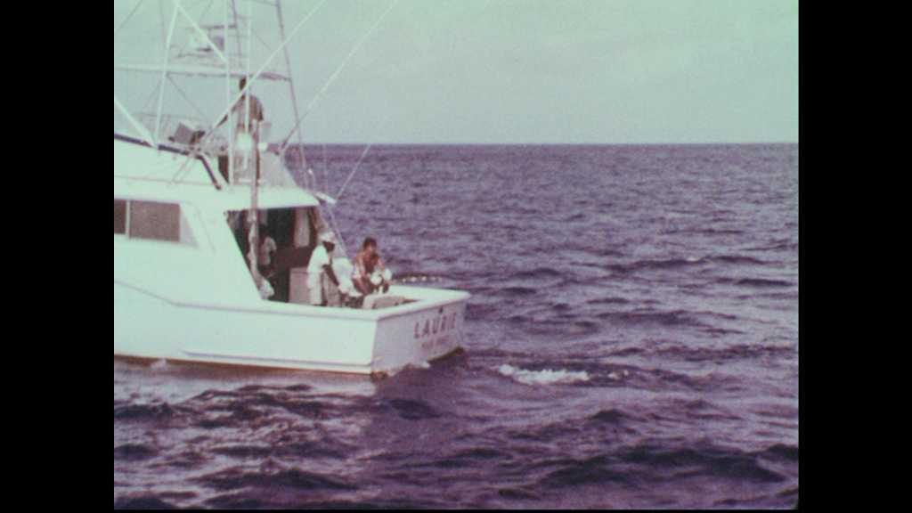 1960s: Men fish off back of boat in ocean. Man reels in fishing line. Fishing line in water. Fishing pole bends.