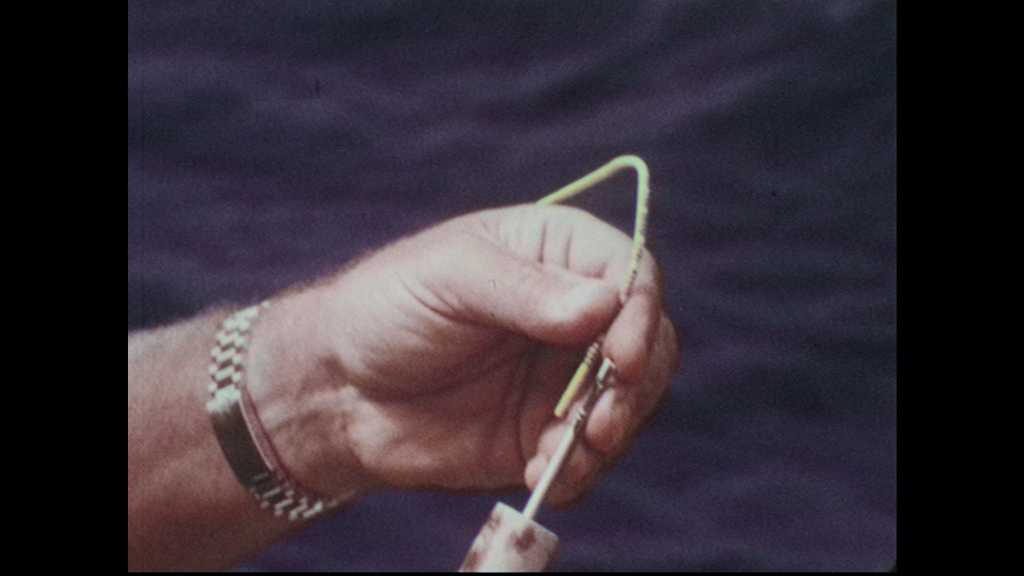 1960s: Man pushes string into needle on pole.