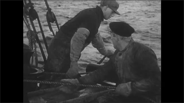1940s: Men haul nets and floats onto fishing vessel. Men pull ropes. Men haul net with fish onto boat.