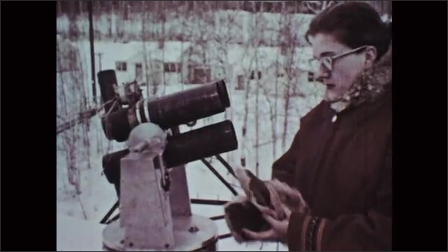 1960s: Woman scientist in parka and glasses climbs to the top of observatory watchtower and checks the camera equipment.