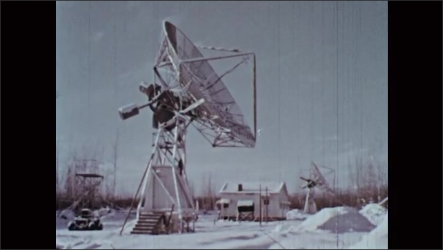1960s: Satellite dishes move and tilt in a winter landscape. Readout recorded on paper by machine. Army airplane takes off. Technician adjusts machinery on the airplane.