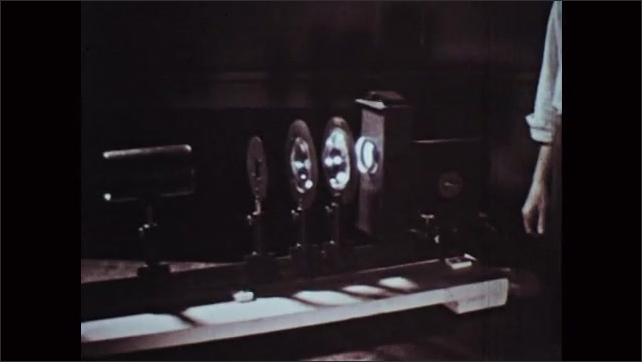 1960s: Man sets up a series of lens and cameras with a light source.