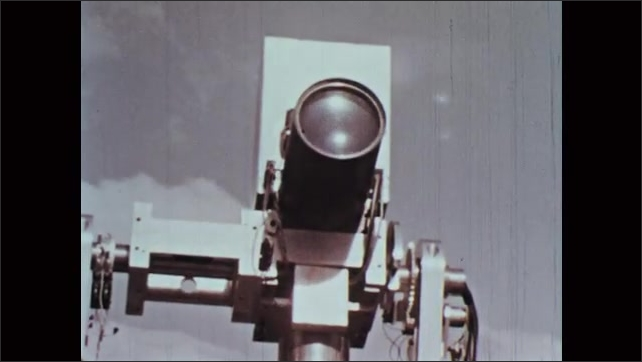 1960s: Truck is unloaded into the desert. Man looks through bubble in observatory roof. Camera tilts down away from the sun. Antenna turns in the blue sky.