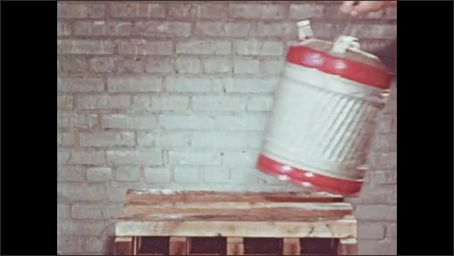 1950s: Man connects hand pump apparatus from oil drum to safety container, cranks pump. Hand sets metal container on table. Man pours oil from safety container to smaller container.