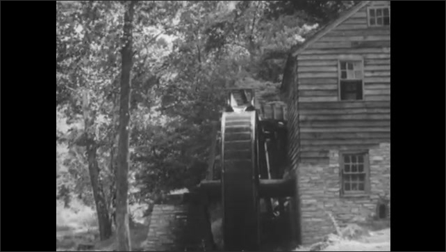 1800s: men in floppy hats chop away at notches in tree trunks with large axes in a dense forest. wheat plants blow in the wind. water wheel turns on mill. corn grows in field and fruit in orchard.