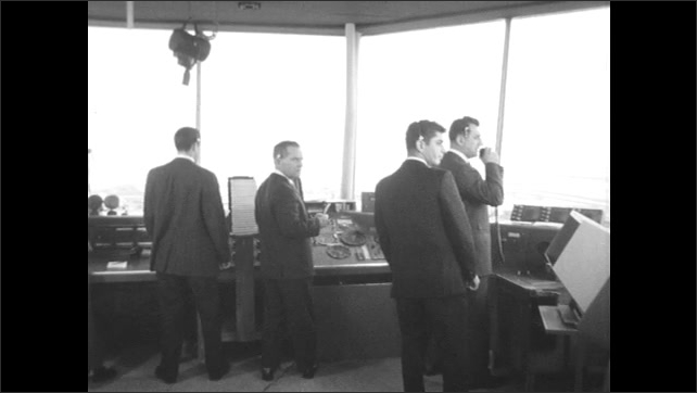 UNITED STATES 1960s: tall building / men working / close up of airplane wing
