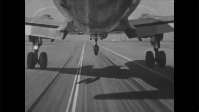 UNITED STATES 1960s: 2 pilots talking / dials / close up of wheels of airplane lifting off ground / hand turning a lever / wheels ascending / airplane rises into sky