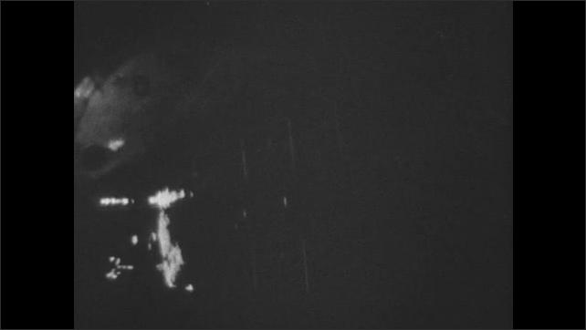 UNITED STATES 1960s: 2 pilots in airplane / flashing lights / man speaking