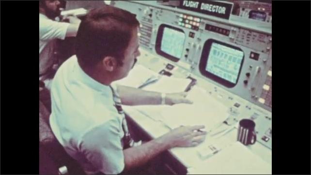 1970s: Man sits in flight simulator cockpit, adjusts controls. Men sit in control room, monitor equipment.