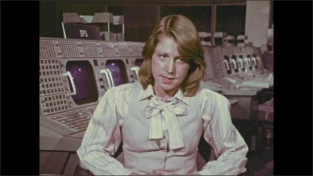 1970s: Woman sits in front of computers and monitors, talks.