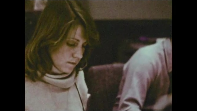 1970s: Woman talks on headset, looks at papers.