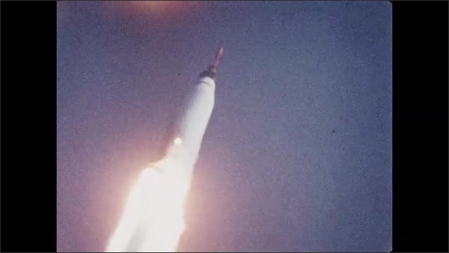 1960s: UNITED STATES: rocket takes off from launch pad. Smoke behind rocket in sky. Astronaut during research session.