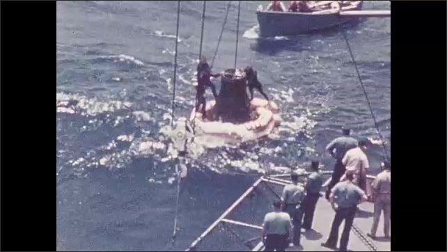 1960s: UNITED STATES: ship at sea. Carrier waits to rescue astronaut. Capsule rescued from sea. Faith 7 capsule lifted from sea.