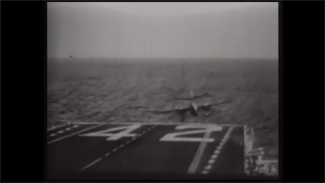 1990s: Jet landing on aircraft carrier. Man waving flags. Plane landing in water past runway. Man covers face. Plane crashes on runway. Plane crashes into ship.