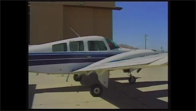 1990s: Plane taxiing on runway. Plane taxiing next to hangar, tracking shot around plane.