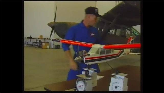 1990s: Man in hangar with model plane, puts model on scale, sets level on model.