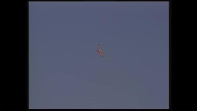 1990s: Pan of model plane flying. Model plane flying overhead.