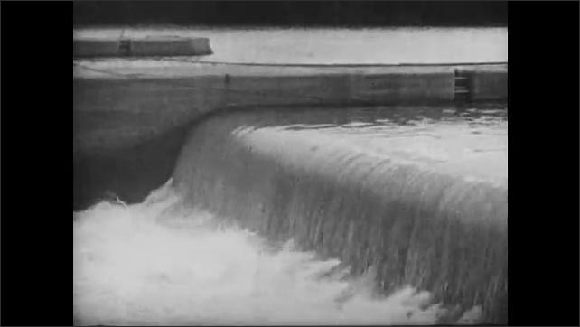 1930s: Man crosses river on zip line. Water flows over dam.