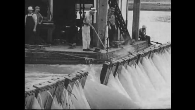 1930s: Workers lower wickets of dam.