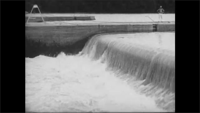 1930s: Water flows over dam.