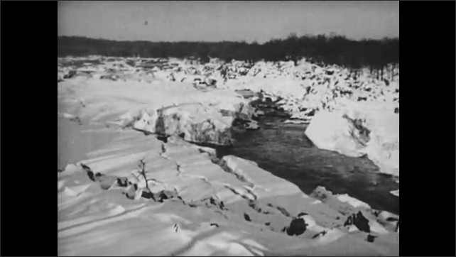 1930s: Snowy banks and river. Water flows through river rapids.