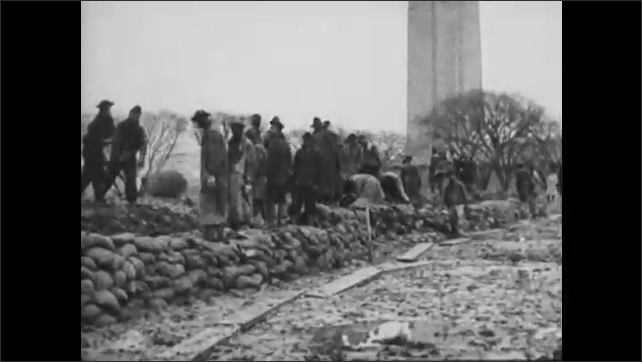1930s: Workers pile up sandbags.