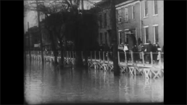 1930s: Newspaper headlines. People walk on raised walkways along flooded street. Woman feeds child. Flooded neighborhood.