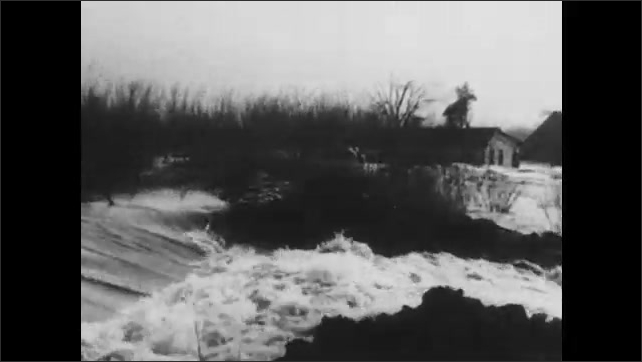 1930s: Men watch flood. Floodwaters gush over land.