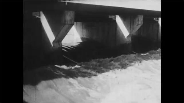 1930s: Water flows through dam.