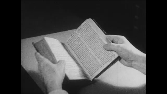1930s: Man picks up book and pages through it.