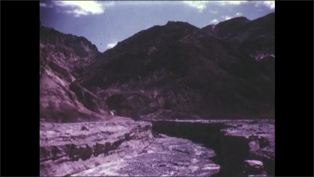 1950s: UNITED STATES: View across mountains in Death Valley desert. River bed in desert. Bushes in desert