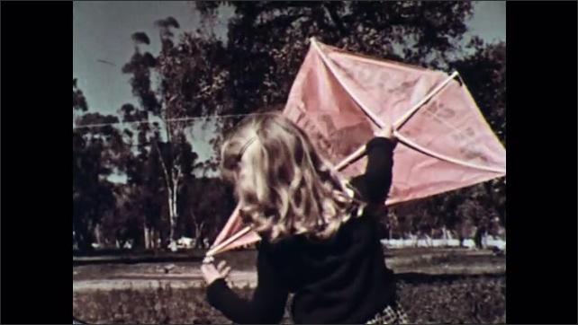 UNITED STATES 1950s : Girl holds kite/ Girl talks to boy