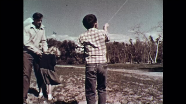 UNITED STATES 1950s : Boy flying kite/ Man and girl watch/ Shot of kite in the sky