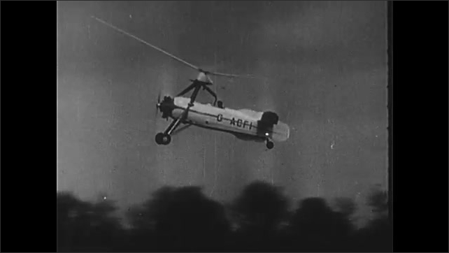 1950s: Hindenburg burns rapidly. Early helicopters fly. Man gets strapped into machine.