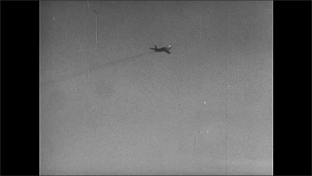 1950s: Jets fly through air. Man films jet, spins around.