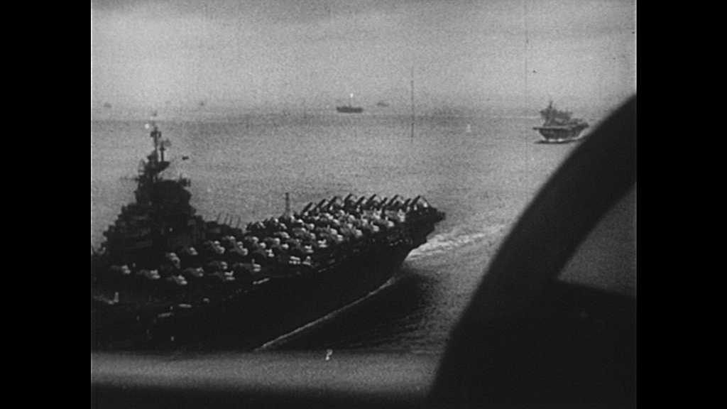1950s: Aircraft carriers in water, jet planes fly overhead. Kamikaze planes dives towards battleship. Guns fire at plane.