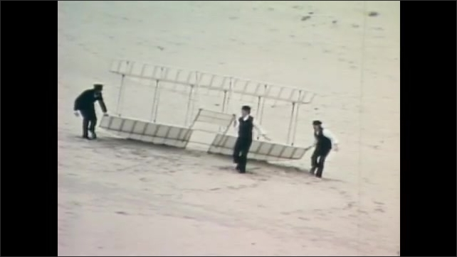 1980s: Wright brothers reenactors carry their airplane wings out onto the dunes. They do a test run with the wings.