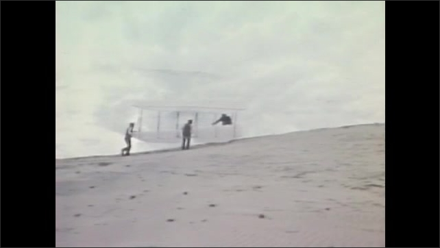 1980s: View from a plane flying in a loop. Wind blows across a sand dune. Wright brothers reenactors set up their flying machine. They run down a dune and one man stops to look as they release it.